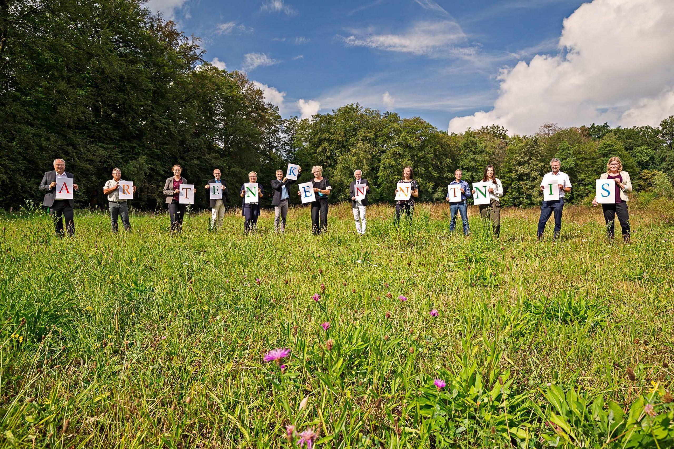 Die dreizehn Anwesenden halten jeweils einen Buchstaben in den Händes und bilden so das Wort Artenkenntnis.